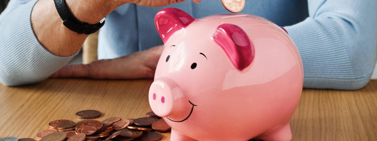 Senior woman inserting coins into piggybank